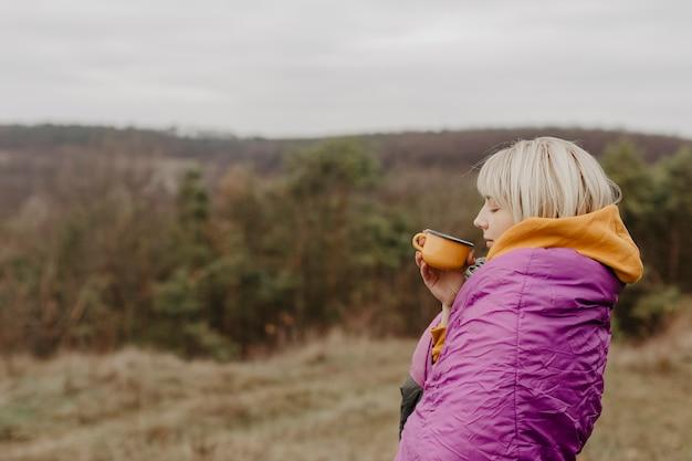 Frau, die naturanblick mit tasse tee genießt
