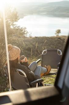 Frau, die neben auto während eines straßenausflugs entspannt