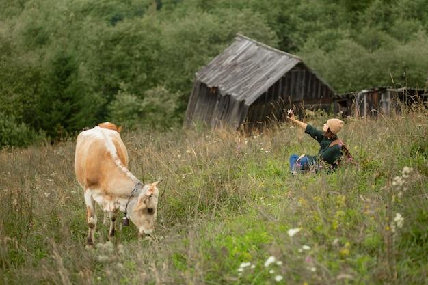 Frau, die neben einer kuh ein foto macht