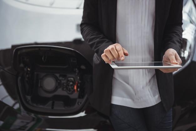 Frau, die neben elektroauto steht und digitales tablett verwendet