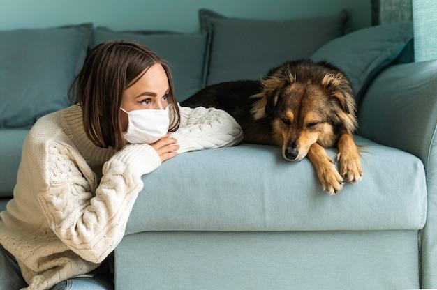 Frau, die neben ihrem hund zu hause während der pandemie sitzt