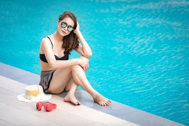 Frau, die neben swimmingpool legt