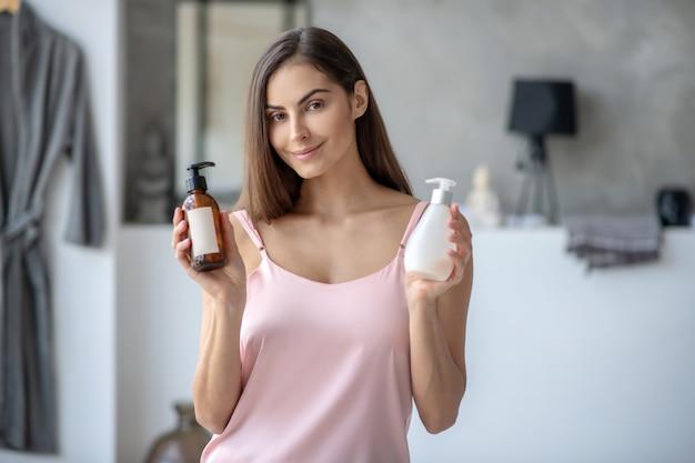 Frau, die neue flaschen der körperlotion zeigt