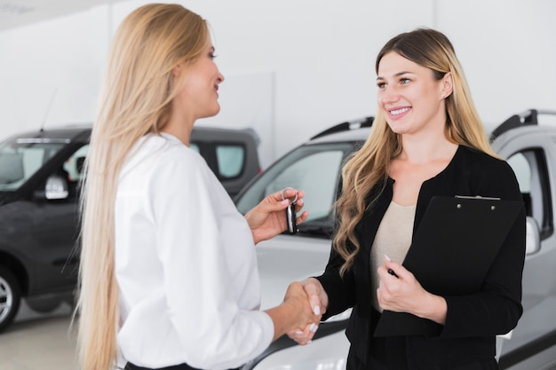 Frau, die neues auto an der verkaufsstelle kauft