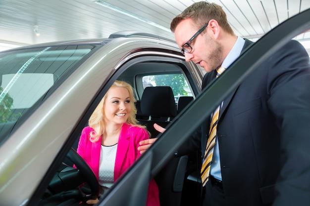 Frau, die neues auto in der autovertretung kauft