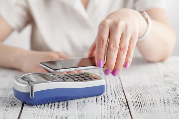 Frau, die nfc-technologie verwendet, um zahlung zu leisten