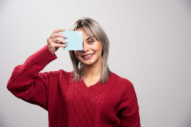 Frau, die notizblock auf grauem hintergrund zeigt.