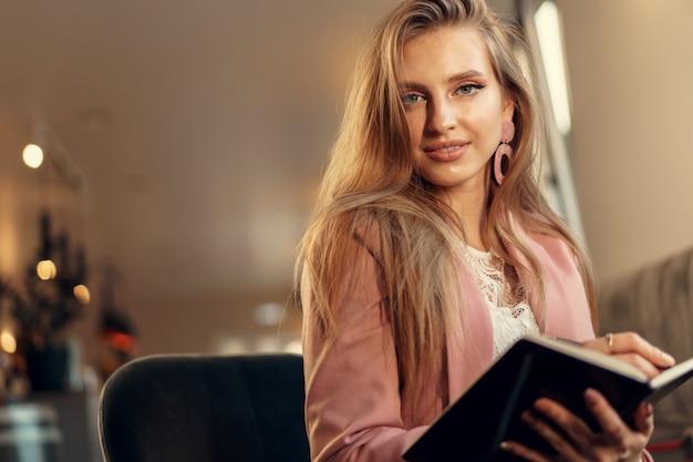 Frau, die notizen macht, während in einem kaffeegeschäft sitzen