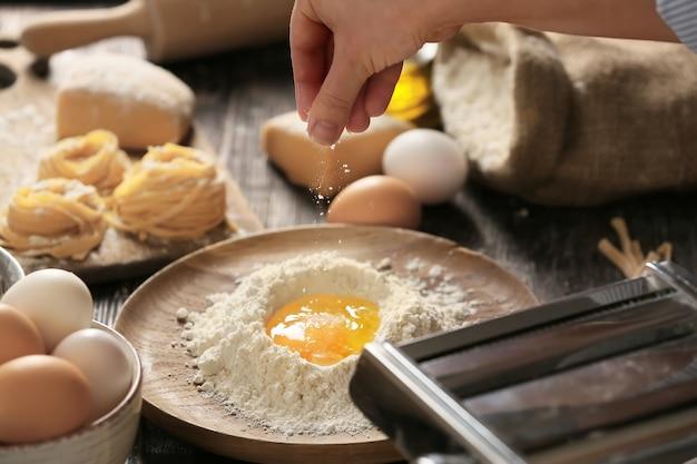 Frau, die nudeln in der küche, nahaufnahme vorbereitet
