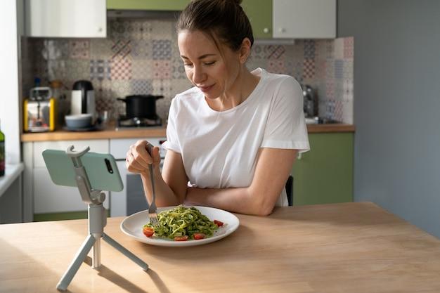 Frau, die nudeln mit vegetarischer pesto-soße isst und film auf smartphone auf stativ zu hause sieht.