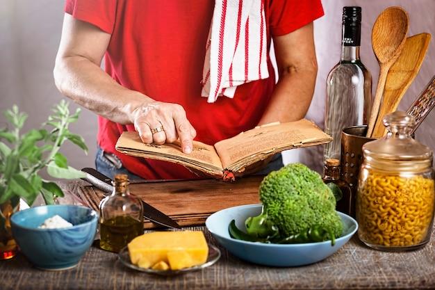 Frau, die nudeln mit weißer sahnesauce zu hause in der küche kocht