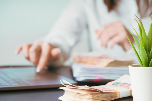 Frau, die oben an der bürohandlung auf tastaturabschluß arbeitet. geld nachzählen