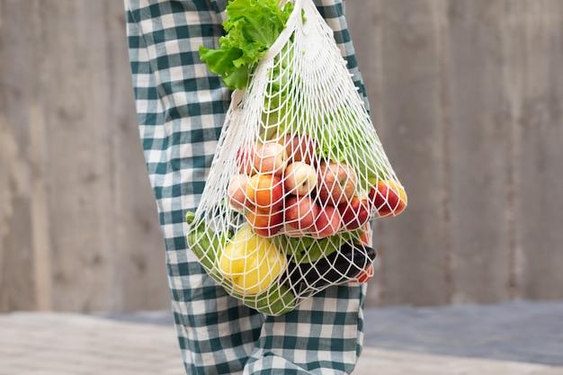 Frau, die obst und gemüse mit wiederverwendbarer baumwolle eco-erzeugnistasche geht und kauft. zero waste lifestyle-konzept