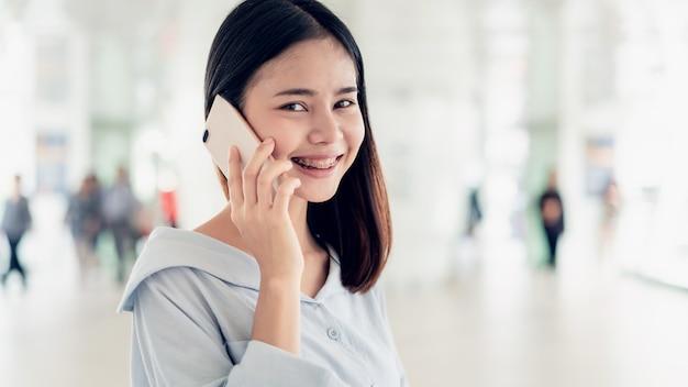 Frau, die öffentlich smartphone auf bereichen des treppenhauses, während der freizeit verwendet. das konzept der verwendung des telefons ist im alltag unerlässlich.
