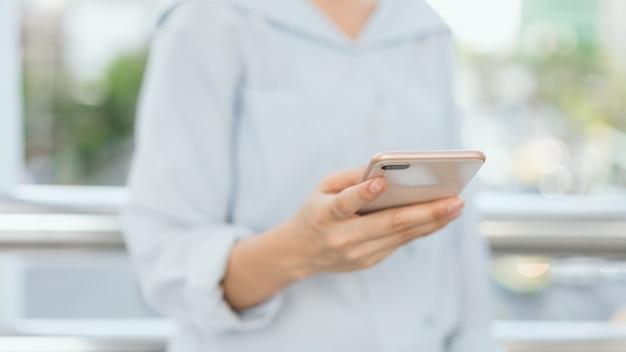 Frau, die öffentlich smartphone auf bereichen des treppenhauses, während der freizeit verwendet.