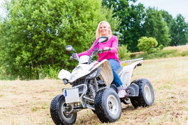 Frau, die off-road mit quad oder atv fährt