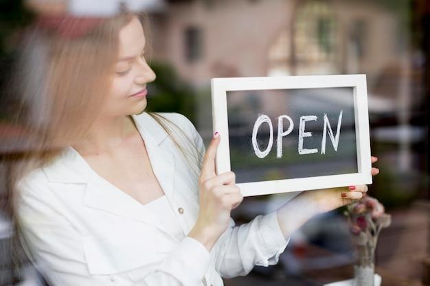 Frau, die offenes zeichen im kaffeehausfenster hält