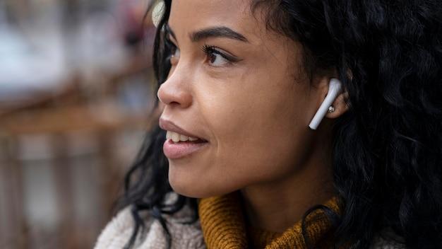Frau, die ohrhörer trägt, um musik zu hören