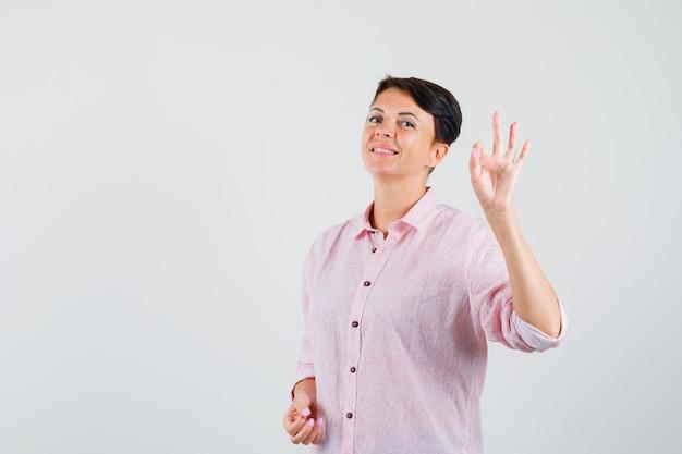 Frau, die ok geste im rosa hemd tut und zuversichtlich schaut. vorderansicht.