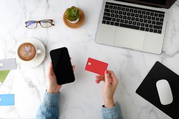 Frau, die online auf der handyanwendung mit der roten kreditkarte einkauft. flache lage und moderner stil