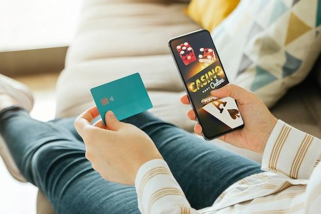 Frau, die online casino mit einem telefon spielt und eine kreditkarte hält, um zu zahlen
