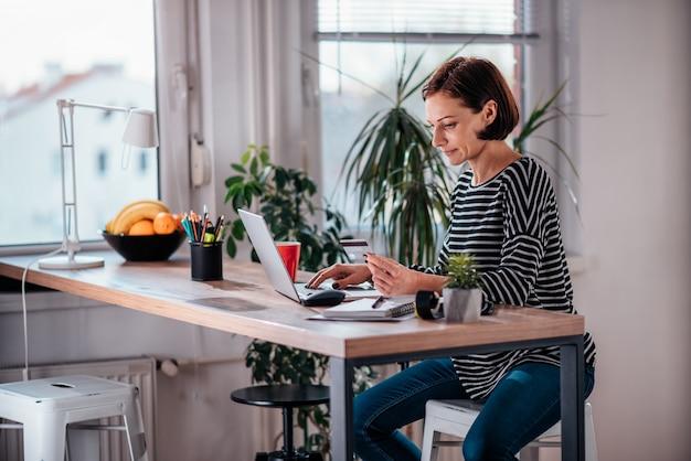 Frau, die online kauft und kreditkarte verwendet