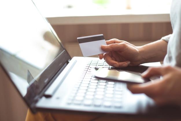 Frau, die online mit einem smartphone kauft. hände der frau kauft online das halten einer kreditkarte mit einem laptop auf dem tisch, der in einem café sitzt.