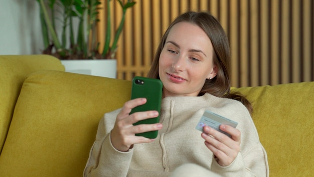Frau, die online mit einer kreditkarte und einem smartphone kauft, die auf einer gelben couch zu hause sitzen