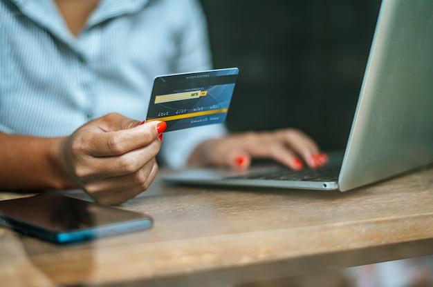 Frau, die online mit einer kreditkarte zahlt