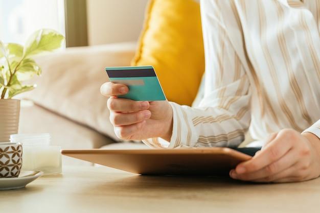 Frau, die online mit ihrem tablet und einer kreditkarte vom wohnzimmer einkauft
