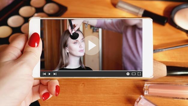 Frau, die online-training für professionelle maskenbildner beobachtet. video-lektion