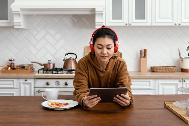 Frau, die online-videos auf tablette hört