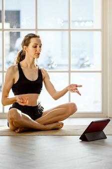 Frau, die online-yoga mit tablette praktiziert