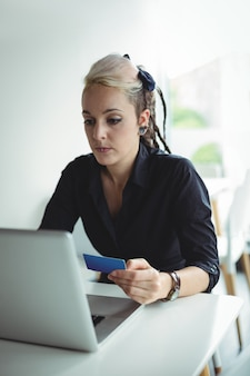 Frau, die online zahlung unter verwendung des laptops und der kreditkarte leistet