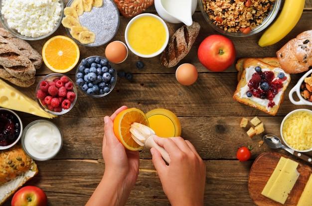 Frau, die orange frucht zusammendrückt und saft bildet. müsli, nüsse, früchte, beeren, milch, joghurt, saft, käse.