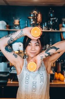 Frau, die orange hält, hält eine orange mit lächeln.