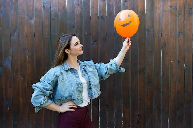 Frau, die orange luftballon in form von halloween-kürbis hält