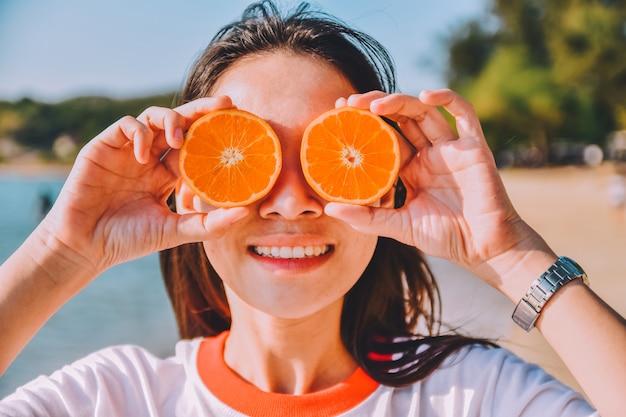 Frau, die orange scheibe am strandseehintergrund, sommerferienweinlesehintergrund hält