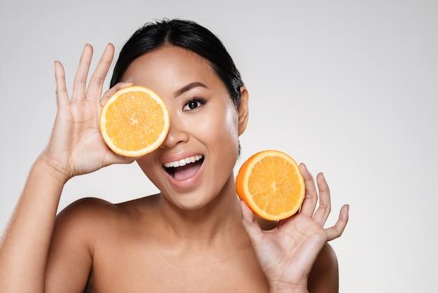 Frau, die orange scheiben nahe ihrem gesicht hält