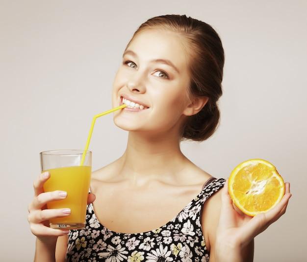 Frau, die orange und orangensaft hält