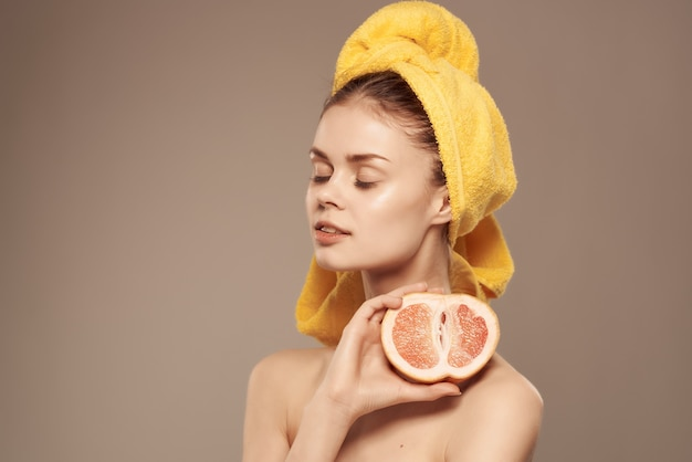 Frau, die orange vitamine hält, säubern hautbadekurortbehandlungen