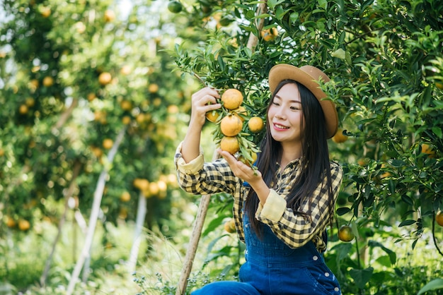 Frau, die orangenplantage hat