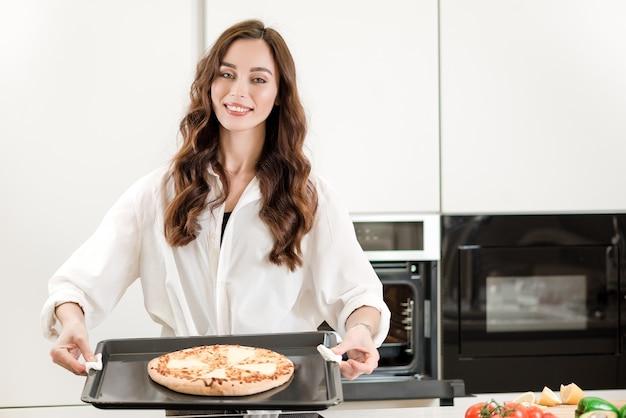 Frau, die orientalischen pizzateller an der küche kocht