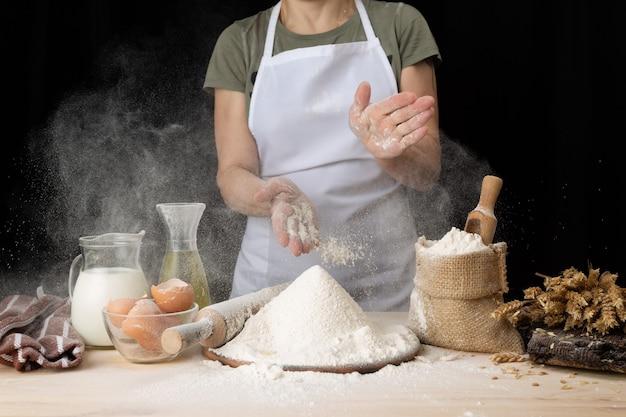 Frau, die ostern backt zu hause bäckerei. frau, die brotteig auf einem holztisch in einer bäckerei in der nähe vorbereitet