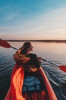 Frau, die paddel in einem kajak auf dem fluss hält