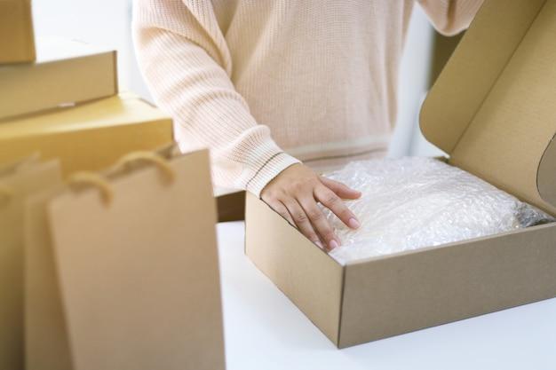 Frau, die paket für lieferung vorbereitet