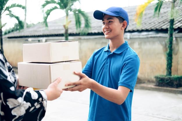 Frau, die paket vom lieferbote empfängt.
