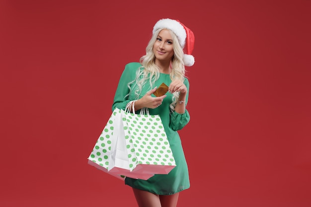 Frau, die pakete und eine kreditkarte hält. weihnachtseinkauf