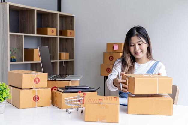 Frau, die paketkästen hält, um kundenadressinformationen zu schreiben, bevor sie über private transportdienste an kunden versendet wird, sie arbeitet online, sie verkauft über die website. konzept für den online-verkauf.