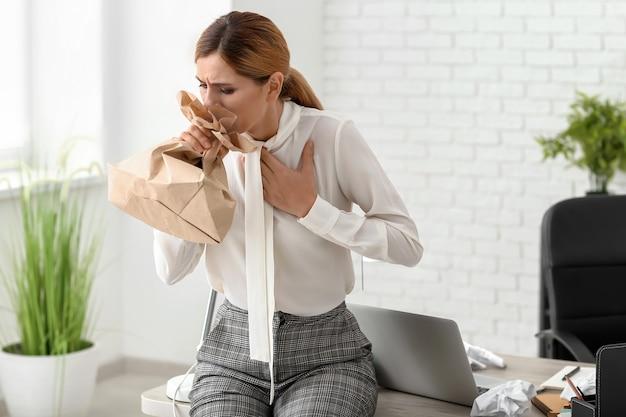 Frau, die panikattacke am arbeitsplatz hat